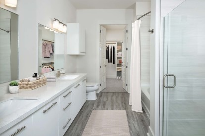 Luxury Ensuite Bathroom with double vanity, large soaking tub, stand up shower, and walk-in closet