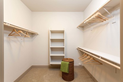 Expansive walk in closet with built in wooden shelves and hanger rods