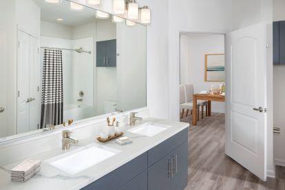Bathroom with Moen fixtures, quartz countertops, and double sink gray vanity with brushed nickel hardware.
