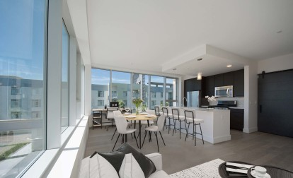 Open concept apartment with large windows bar seating and space for a desk
