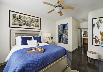 Bedroom with concrete flooring ceiling fan and ensuite bath