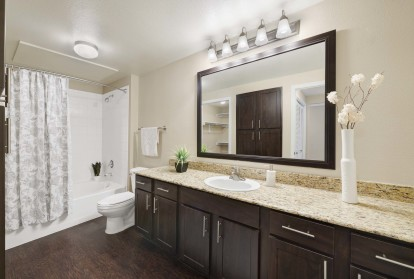 Vista style bathroom with granite countertops bathtubs with curved shower rods and espresso cabinets