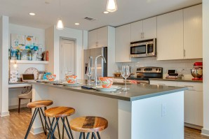 Kitchen island with gray countertops and barstools