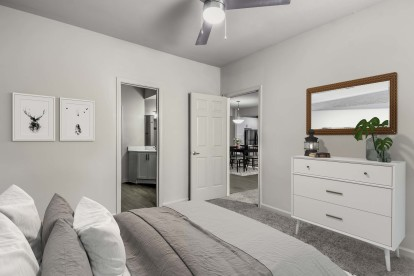 Modern style bedroom with ensuite bathroom carpet flooring and ceiling fan
