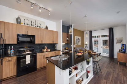 Black granite finishes kitchen with island and black appliances