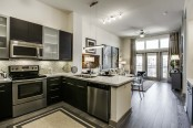 Kitchen with quartz countertops cabinets with frosted glass doors and stainless steel appliances