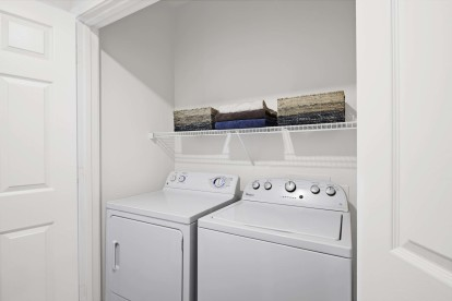 Laundry closet with side by side washer and dryer and shelf