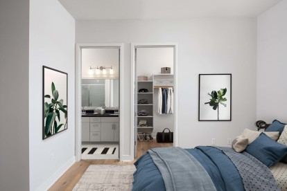 Penthouse bedroom with wood look flooring high ceilings and large walk in closet
