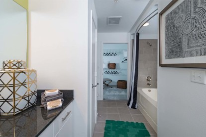 Bathroom with curved shower rod and walk in closet