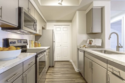 One bedroom kitchen with wood style flooring stainless steel appliances and quartz countertops