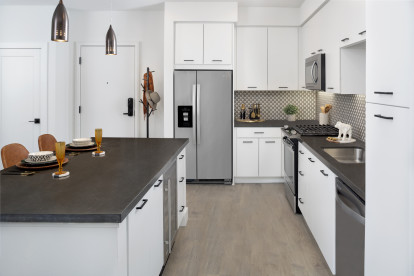 Open concept kitchen living with floor to ceiling windows stainless steel appliances and large island