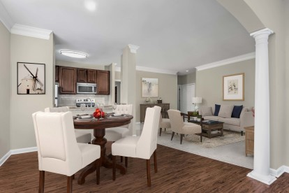 Open concept floor plan with dining and living space crown molding and arched entryways