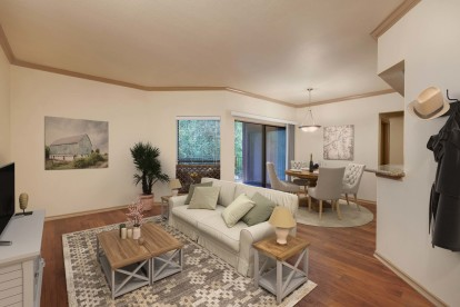 Open concept living and dining room with crown molding wood look flooring and patio access
