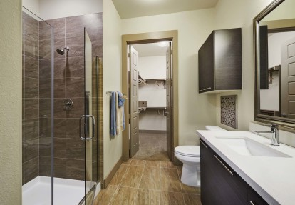 Bathroom with glass enclosed shower walk in closet and tile flooring