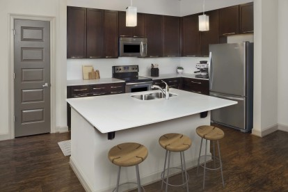 Terrace kitchen with white quartz countertops, stainless steel appliances, and hardwood-style flooring