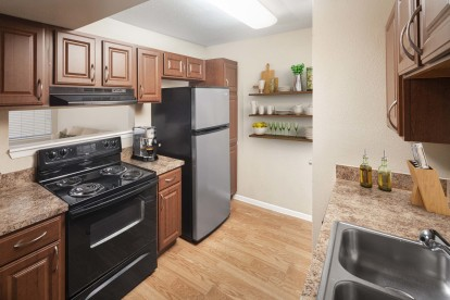 Kitchen with black appliances wood look flooring chestnut cabinets and laminate countertops