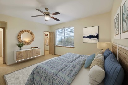 Bedroom with walk in closet ceiling fan and carpet flooring