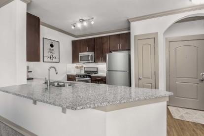 Kitchen with large island, hardwood-style flooring, and undermount sink.