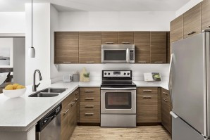 Kitchen with quartz countertops stainless steel appliances and glass cooktop