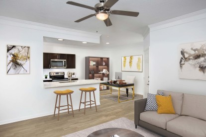 Open concept living with work from home space wood look flooring crown molding and ceiling fan