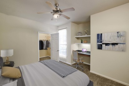 Bedroom with walk in closet built in desk carpet flooring and ceiling fan