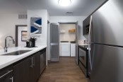 Modern style kitchen with stainless steel appliances and white countertops and full size washer and dryer