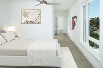 Main bedroom with seven-and-a-half-inch white oak hardwood flooring, multiple windows, and a ceiling fan