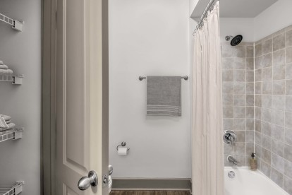 Bathroom with linen closet and bathtub and shower combination with tile surround