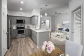 Open-concept dining and living area near contemporary kitchen with stainless steel appliances