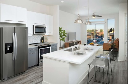 Kitchen with bar seating and white quartz countertops