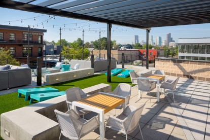 Rooftop Lounge with dining areas, corn hole, and city views