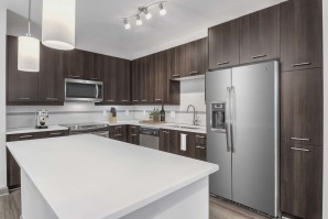 Kitchen with white quartz countertops, pendant lighting, and sleek gray cabinets