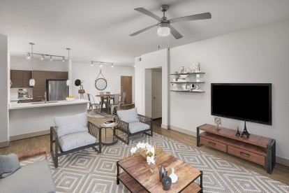 Open concept floor plan living dining and kitchen with wood look flooring ceiling fan and track lighting