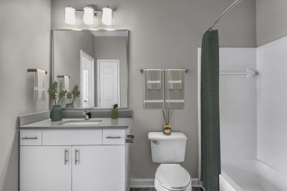 Bathroom with quartz countertop undermount sink and bathtub with curved shower rod