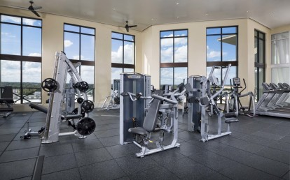 Rooftop fitness center with cardio equipment overlooking lake concord