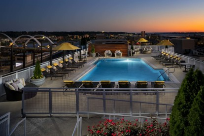 Dusk view of rooftop swimming pool and entertainment lounge