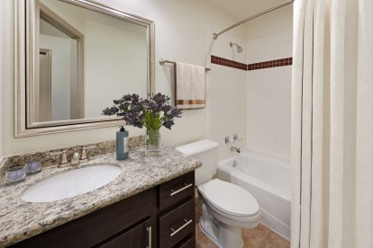Bathroom with granite counters tile floor and bathtub with tile surround and curved shower rod