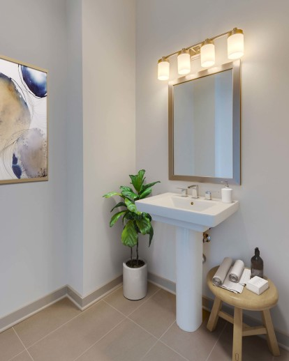 Camden Music Row Apartments Penthouse bathroom with pedestal sink, tile floors, and designer lighting