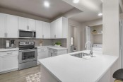 Modern style kitchen alongside laundry room with full size washer and dryer