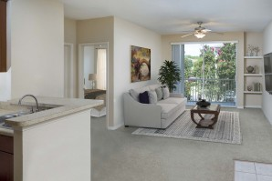 Open-concept living room with built-in bookshelves, ceiling fan, and private balcony