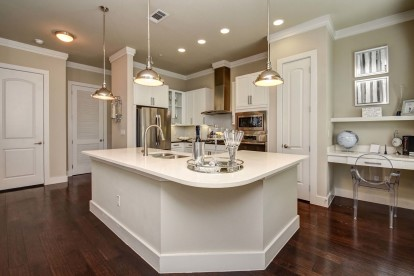 The townhomes kitchen with stainless steel appliances, white quartz countertops and cabinets, curved island, and built-in desk