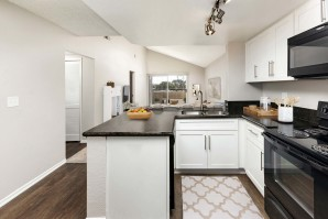 Kitchen with granite countertops black appliances undermount sink and wood look flooring