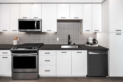 Open-concept kitchen with stainless steel appliances, gray quartz countertops, and timeless ceramic backsplash