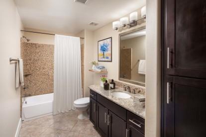 Bathroom with bathtub with tile surround and framed bathroom mirror