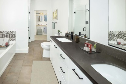Concrete-inspired dual sink vanity in a five-fixture main bathroom with ensuite walk-in closet
