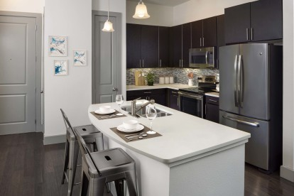 The terrace kitchen with quartz countertops stainless steel appliances and wood look floor