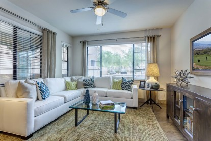 Bright living area with ceiling fan and wood style flooring
