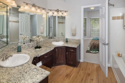 Traditional style bathroom with granite style countertops and double sink vanity