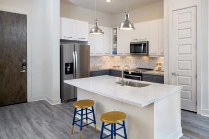 Kitchen with herringbone backsplash, stainless steel appliances, bar seating and white quartz countertops