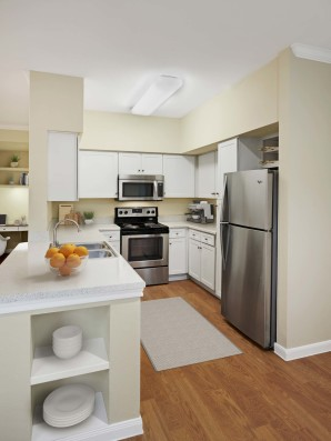 Contemporary finishes kitchen with white cabinets and wood style flooring